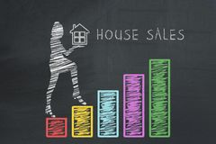 House sales concept. Drawn business woman holding house and climbing up on hand drawn graphs chart diagram columns.  Stock Photo