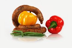 House sausage. Composition from tasty house sausage and green vegetables Stock Image