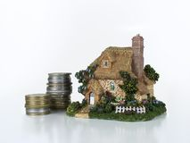 House savings. Small house / home figure with money coins. Good concept for home savings - credit for buying house. Home sweet home, house concept royalty free stock images
