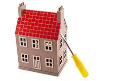 House and screwdriver. Gray house layout with a screwdriver and screws Royalty Free Stock Photo