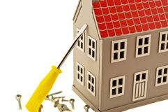 House and screwdriver. Gray house layout with a screwdriver and screws Stock Photo