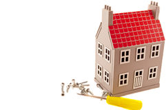 House and screwdriver. Gray house layout with a screwdriver and screws Royalty Free Stock Photos