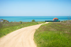 Cottage by the sea. House by the sea on a green hill Royalty Free Stock Images