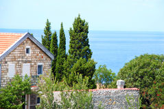 House on seaside. Stone house with red tiled roof between cypresses by adriatic sea Stock Photos