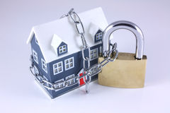 House Security. Small house with chain around it and a large padlock stock images