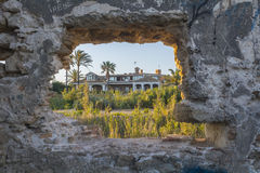 House seen through the hole of a ruined wall Stock Photography
