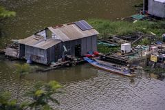 The house is a shack built of tin sheets on the water in Vietnamese fishing village built on the water on Lake Lac stock photo