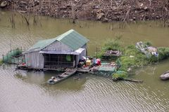 House shack in the middle of the river with a boat and garden. The house is a shack with a green roof in the middle of the river with a boat and a garden. The royalty free stock photos