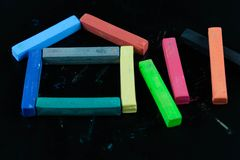 House shape of Colourful chalk pastel on black background. Concept for education stock images