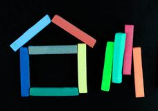 House shape of Colourful chalk pastel on black background. Education concept royalty free stock image