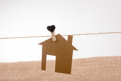 House shape cut out of paper on a string Stock Photo