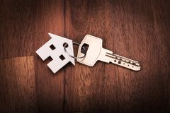 House shape key chain. On wood floor Stock Images