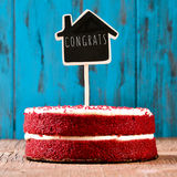 House-shaped chalkboard with the text congrats in a cake, with a. A red velvet cake with a chalkboard in the shape of a house with the text congrats, on a rustic royalty free stock photos
