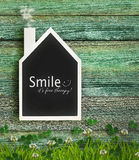 House shaped chalkboard on wood Stock Images