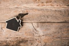 House-shaped key on a wood table stock photos