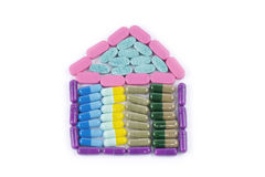 House shaped medicine. Pills, tablets and capsules arranged to form a house shape on white background Royalty Free Stock Photography