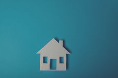 House shaped paper cutout. On on blue background Stock Photos