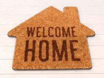 House shaped Welcome mat on wooden floor. Brown house icon shape coir doormat with text print Welcome Home on wooden floor. 3D illustration stock illustration