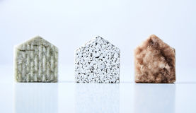 House shapes made from building materials. Three natural coloured, textured house shapes made from building materials isolated on a white background royalty free stock photo