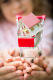 House in shopping cart. Family holding little house in shopping cart. Shallow depth of field Royalty Free Stock Image