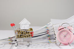 House on shopping cart with gold coins and alarm clock Royalty Free Stock Photos