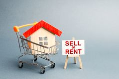 House in a shopping cart and a stand with the inscription sell or rent. rental or selling a home. Real estate liquidity stock photography