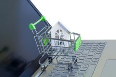 House in the shopping trolley on laptop keyboard. Rent buy or sell real estate Royalty Free Stock Image