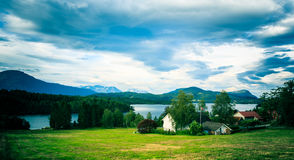 House on the shore against the backdrop of snowy mountains . Royalty Free Stock Photography