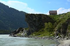 A house on the shore of a mountain river. Royalty Free Stock Photos