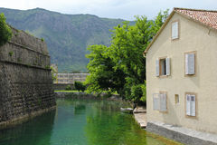 House with shuttered windows, river and mountains in Kotor Stock Photography