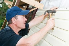 House siding works. Worker planking house with plastic siding panels stock photo