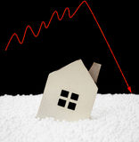 House sinking into polystyrene particle with a downward arrow on background Stock Images