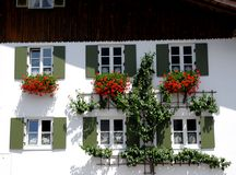House with six windows and red flowers in Oberammergau in Bavaria (Germany) Stock Image