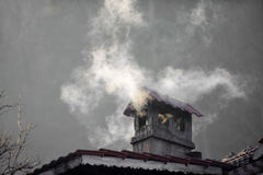 House with smoking chimney Royalty Free Stock Image