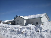 House in snow. The snow plows have been by, and now the houses in the central interior of BC. Canada are almost hidden Stock Photos