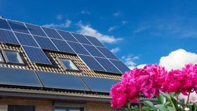 House with solar panels on the roof. With flowers in the garden Stock Image