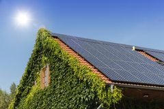 House with solar panels on the roof. Against blue sky and sunlight Stock Photos