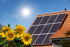 House with solar panels on the roof. And sunflowers in the garden royalty free stock image