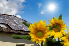 House with solar panels on the roof. And sunflowers in the garden Stock Photo