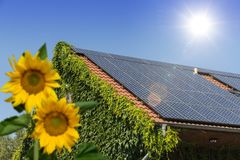House with solar panels on the roof. And sunflowers in the garden Royalty Free Stock Photos
