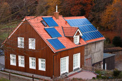 House with solar panels sun heating system on roof. Historic farm house with modern solar electric and solar heating system on large roof Stock Photos