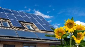 House with solar panels and sunflowers in the garden royalty free stock photo