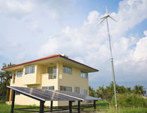 House with solar panels and wind turbines aside stock photo