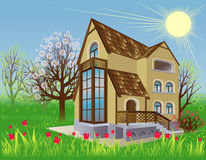 House is in the spring garden. Spring landscape with a beautiful cottage and flowerings trees Stock Images