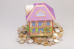 House standing on  heap of coins on gray.Real estate concept Royalty Free Stock Photography