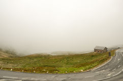 House standing on a mountain in the clouds. Morning fog, mist Stock Photography