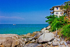 A house stays the seashore. The green sea, the green tree, the sky is blue Stock Image