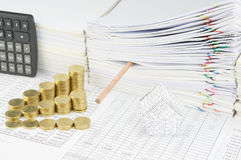 House and step gold coins with pencil put in paperwork Stock Image