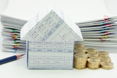 House with step pile of gold coins. And pencil have pile overload document of report with colorful paperclip as background Royalty Free Stock Photo