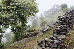 House and stone wall in the fog on the hillside. In Nepalese village in the mountains Stock Photos